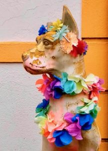 A statue of a dog has a colorful garland of flowers around it's neck.