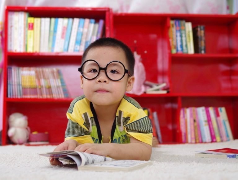 Young boy with big round glasses sits with an open book in front of a red bookcase filled with colorful books.