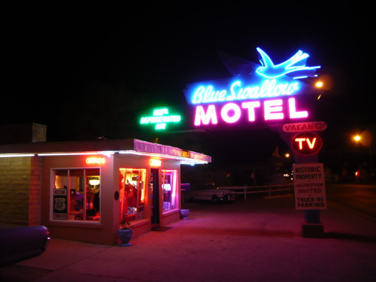 Road trip classic: Blue Swallow Motel neon sign at night on Route 66.