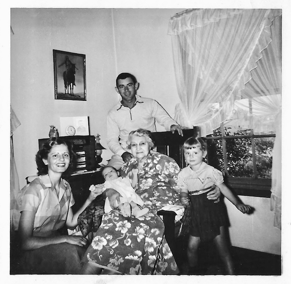 Black and white photograph of a family in 1953 at the end of a road trip. Great-grandmother holding two month old baby girl, father standing behind, mother kneeling and three year old sister standing.